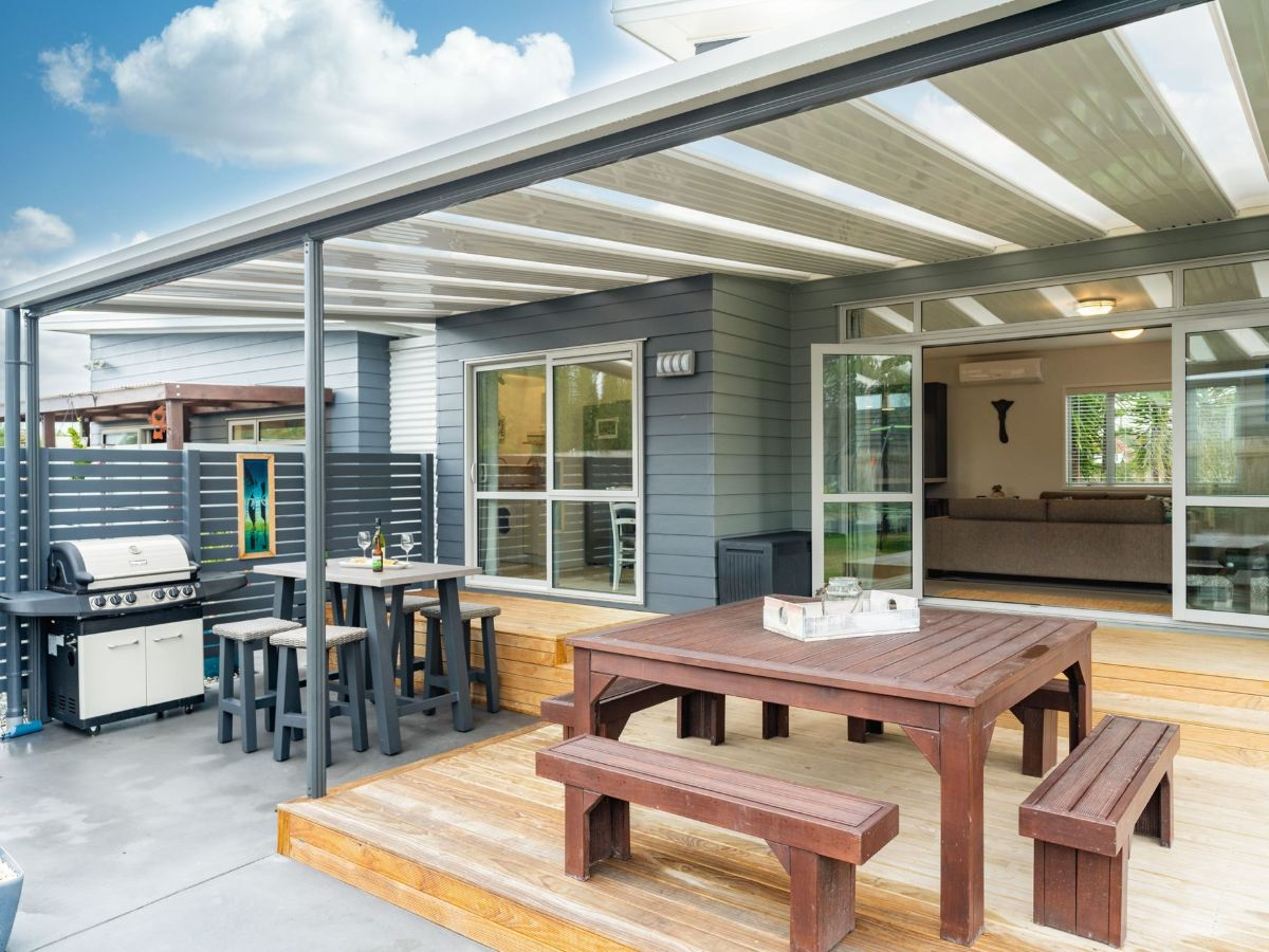 Outdoor entertaining space covered with flat roof and custom powder coated posts and beams