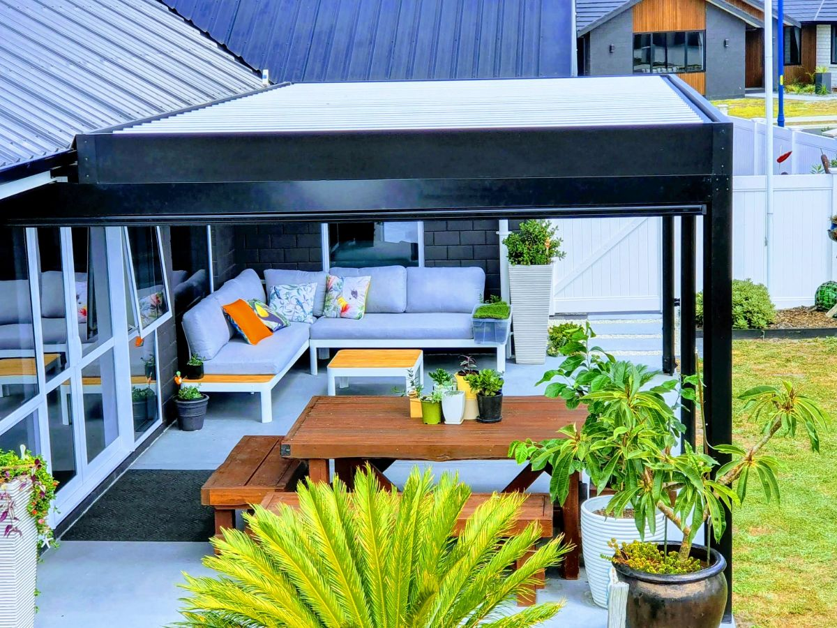 Beautiful outdoor living space covered with black louvre roof