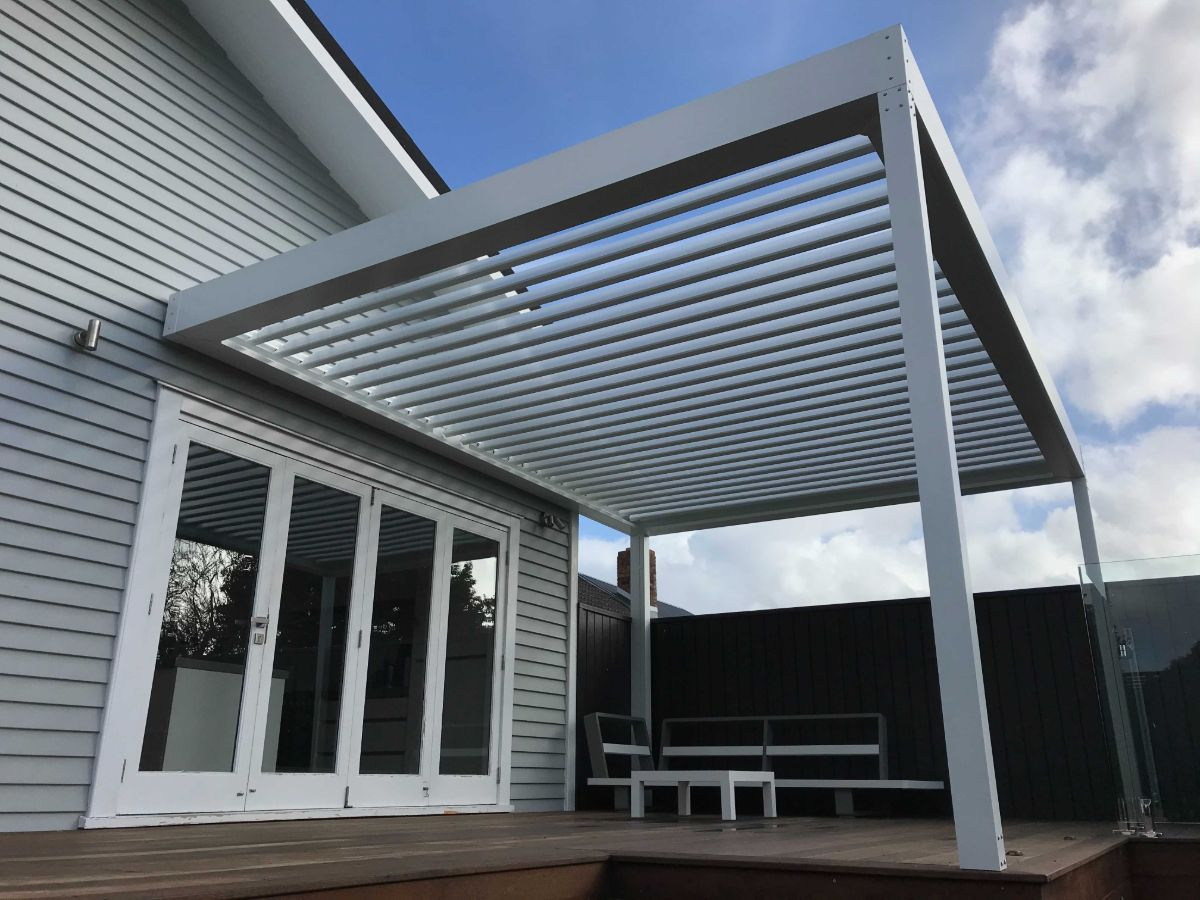 White louvre covering deck outside french doors attached to gable end of house