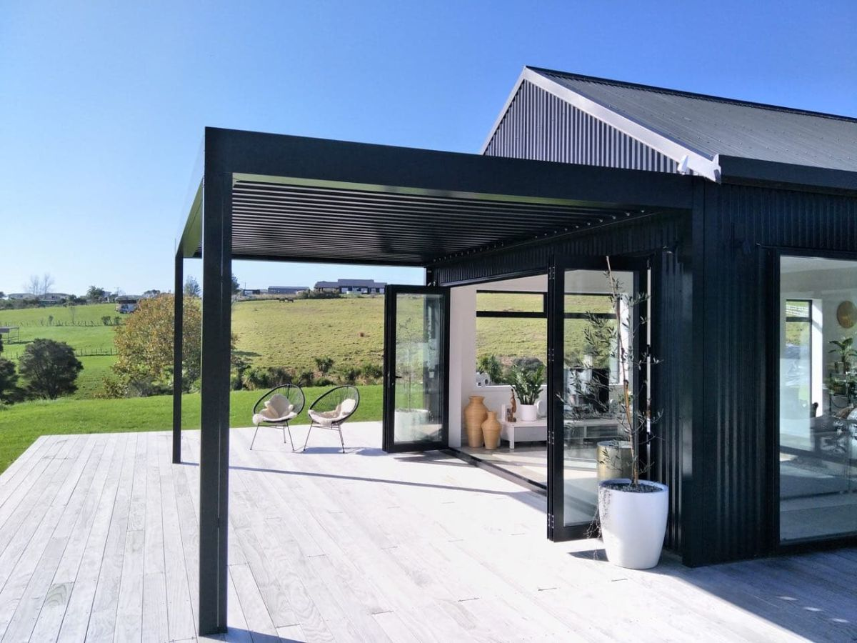 Black louvre roof attached to black house with paddock views