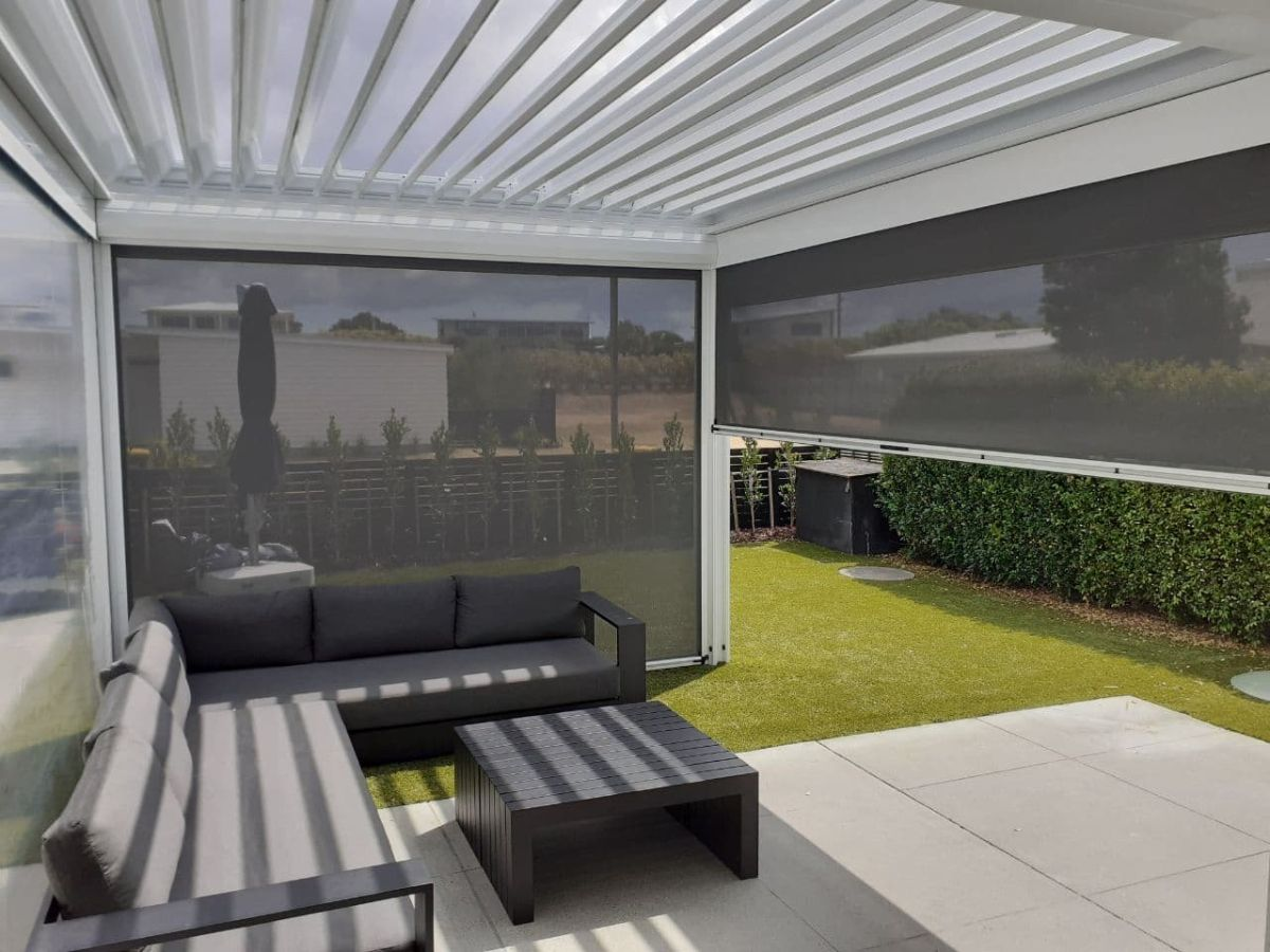 PVC and mesh blinds enclosing white louvre roof