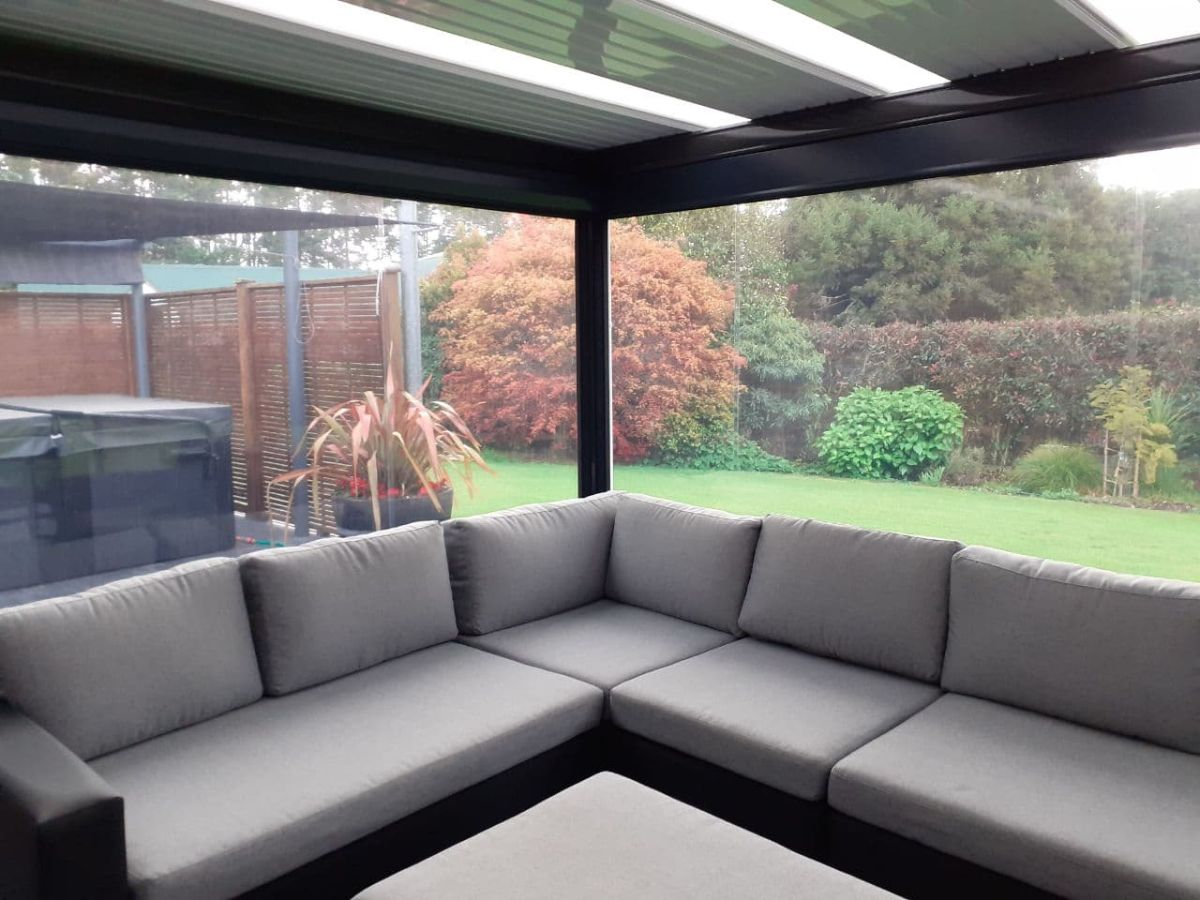 PVC blinds enclosing a flat roof over lounge furniture