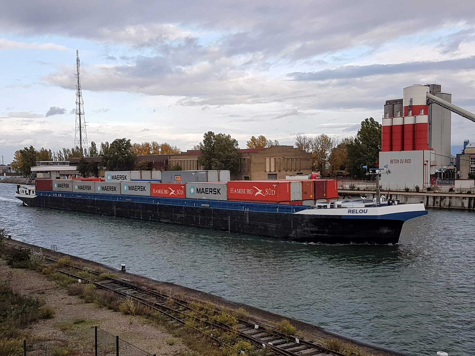 MMR barge ship passing by through the water, filled with containers