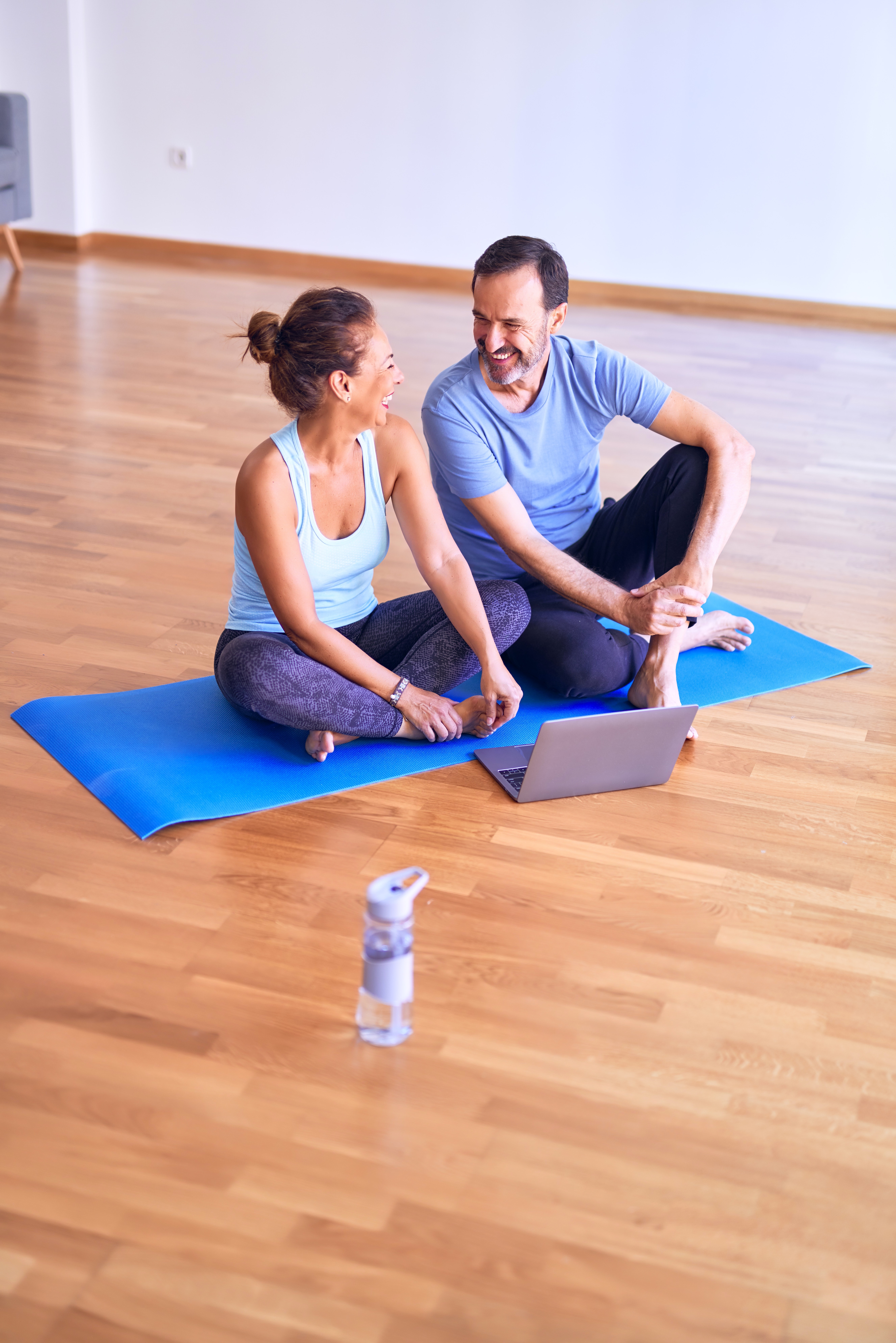 A man and a woman sit on their yoga mat as they get ready to complete an online fitness workout class.