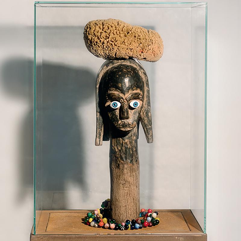 """""""J'accuse"""" Ich klage an! - 2018 - 141x35x23cm, Afrikanische Holzskulptur, Augen aus Kunststoff, Trade Beads (koloniales Zahlungsmittel), Schwamm, Glassturz, Eisentisch. Objektkunst"""