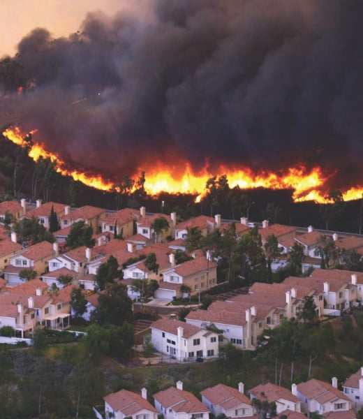 Smoke and flames come over a hill and threaten homes in San Diego