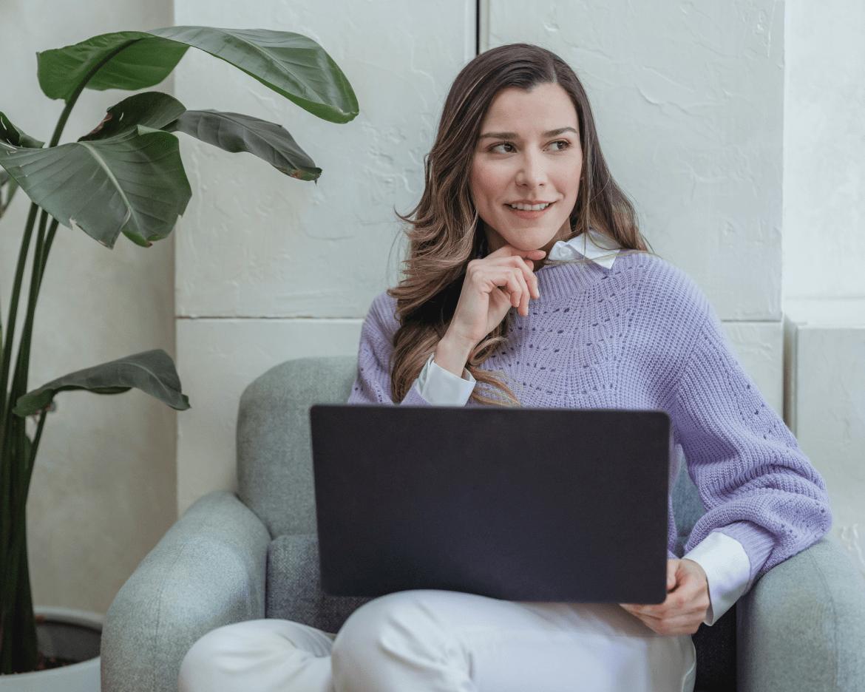 Photo d'une femme assise avec son ordinateur sur les genoux