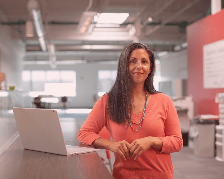 Photo individuelle d'une femme se tenant près de son ordinateur