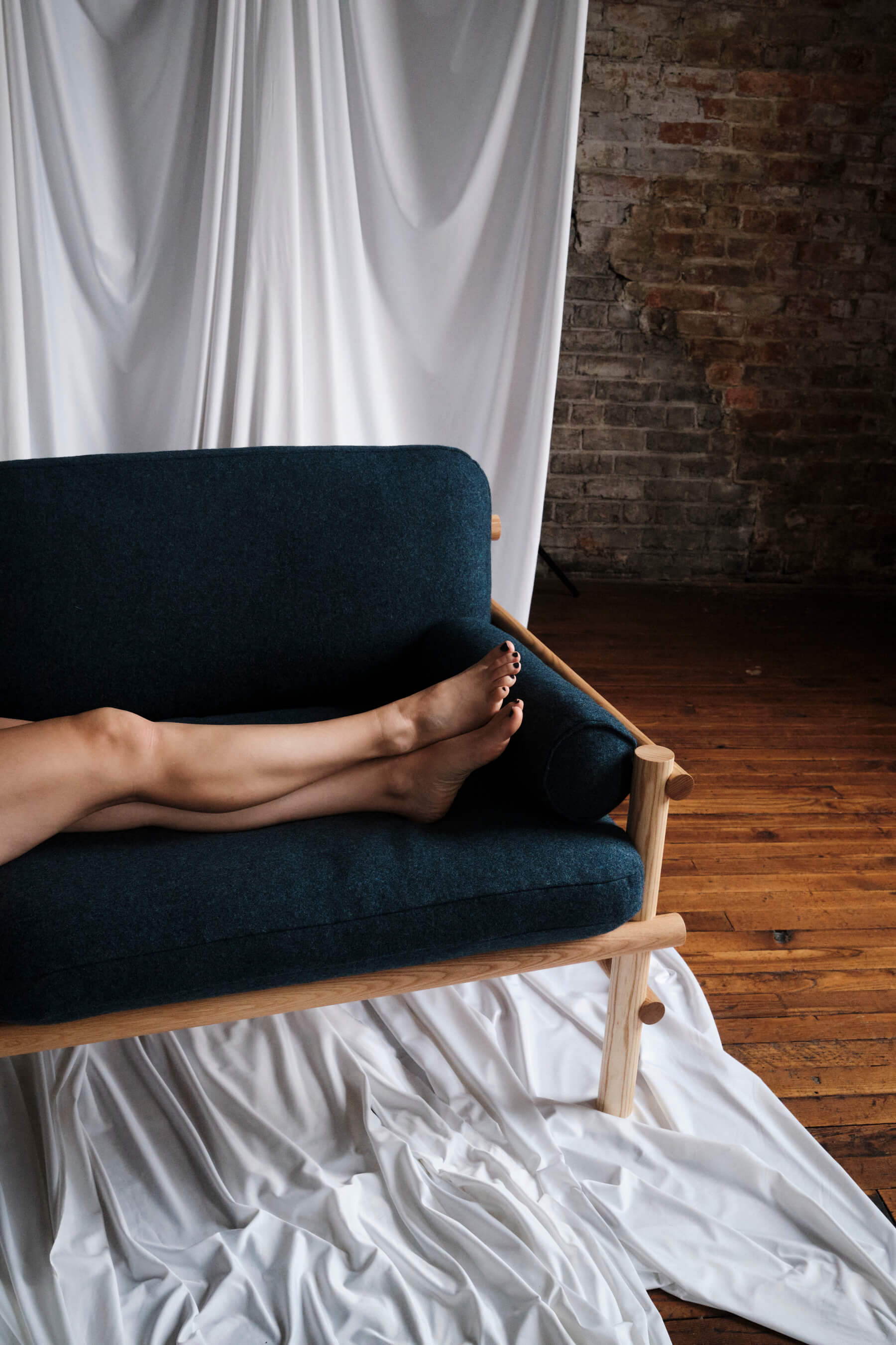 A modern yet vintage looking sofa with an exposed wood frame and blue felt cushions in a old warehouse; a woman has her bare legs up on the sofa, with dark painted nails.