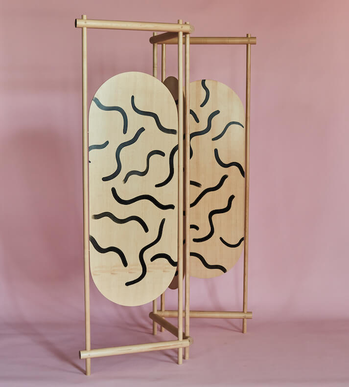 on a pink backdrop a wooden, Scandinavian looking room divider is closely folded together.