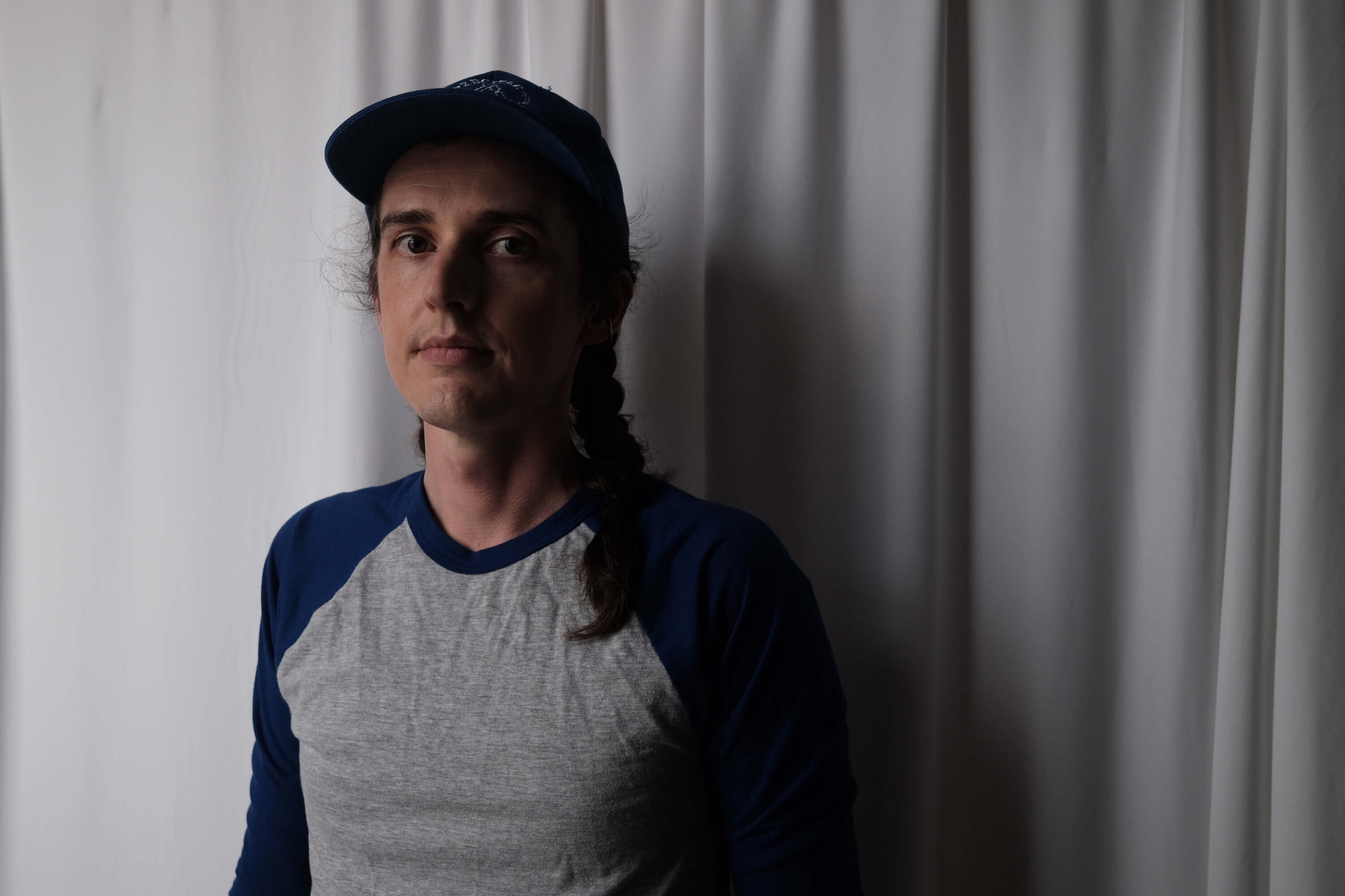 A portrait of Mike, a white person with braided hair, wearing a blue hat and a baseball shirt. They stand in front of a white fabric backdrop.