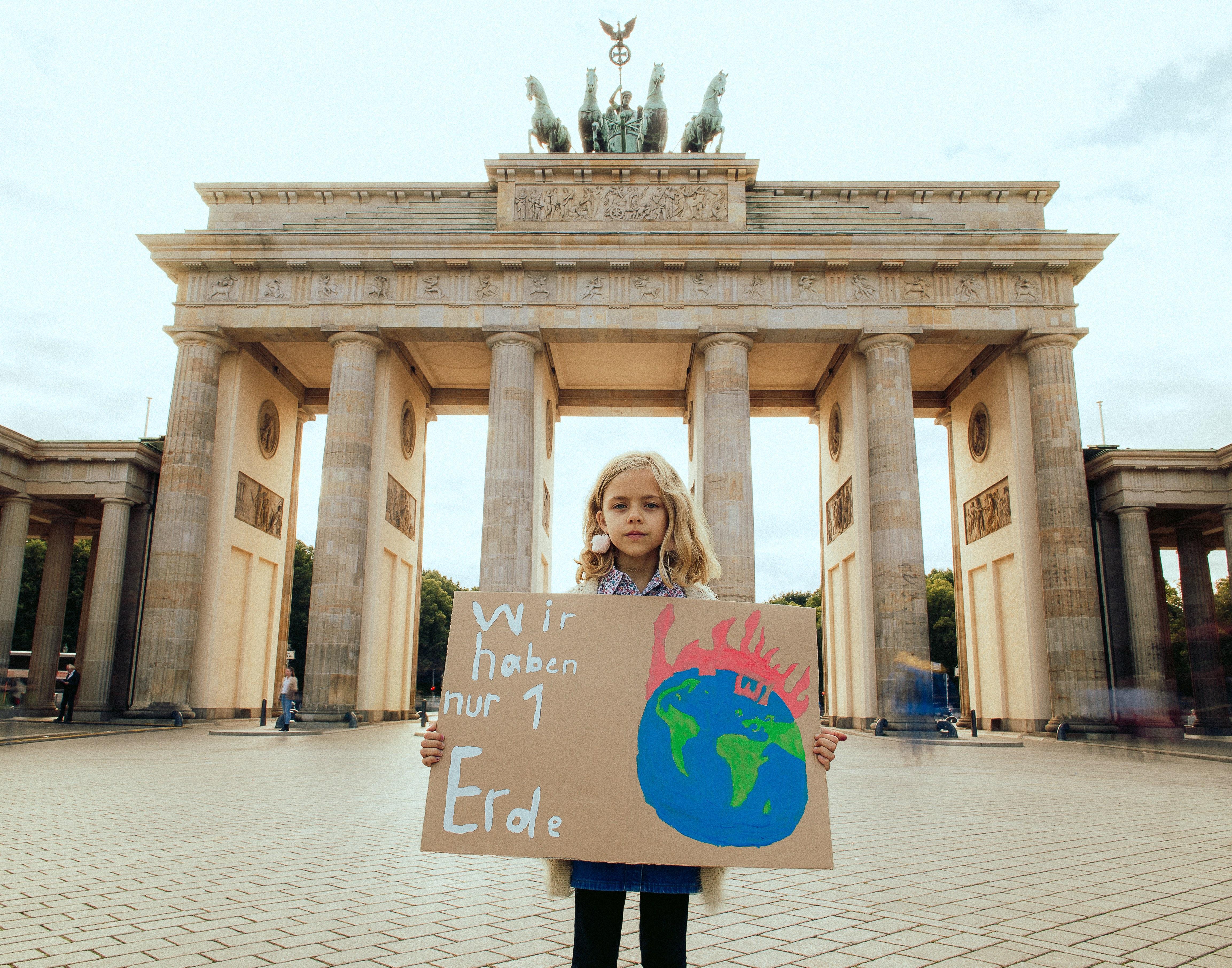 Mia vor dem Brandenburger Tor mit Schild: Wir haben nur 1 Erde.