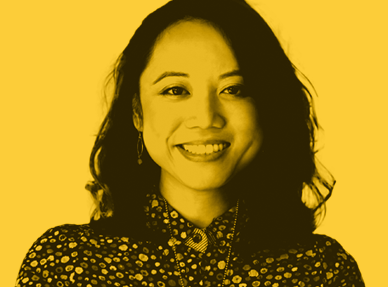 An image of a confident and professional woman. They have a patterned shirt. The image is tinted yellow.