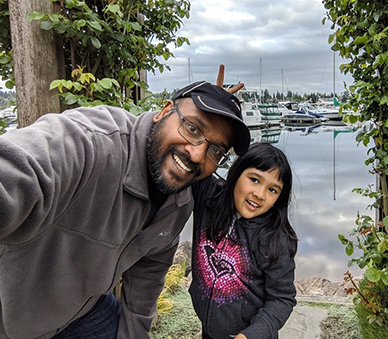 A photo of Bala and his child in front of some boats