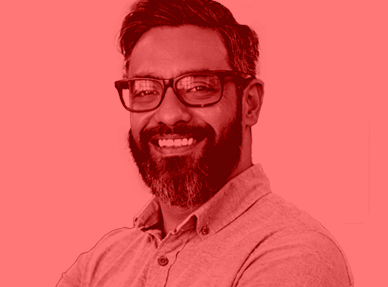 An image of a bearded man with glasses. The image is tinted red.