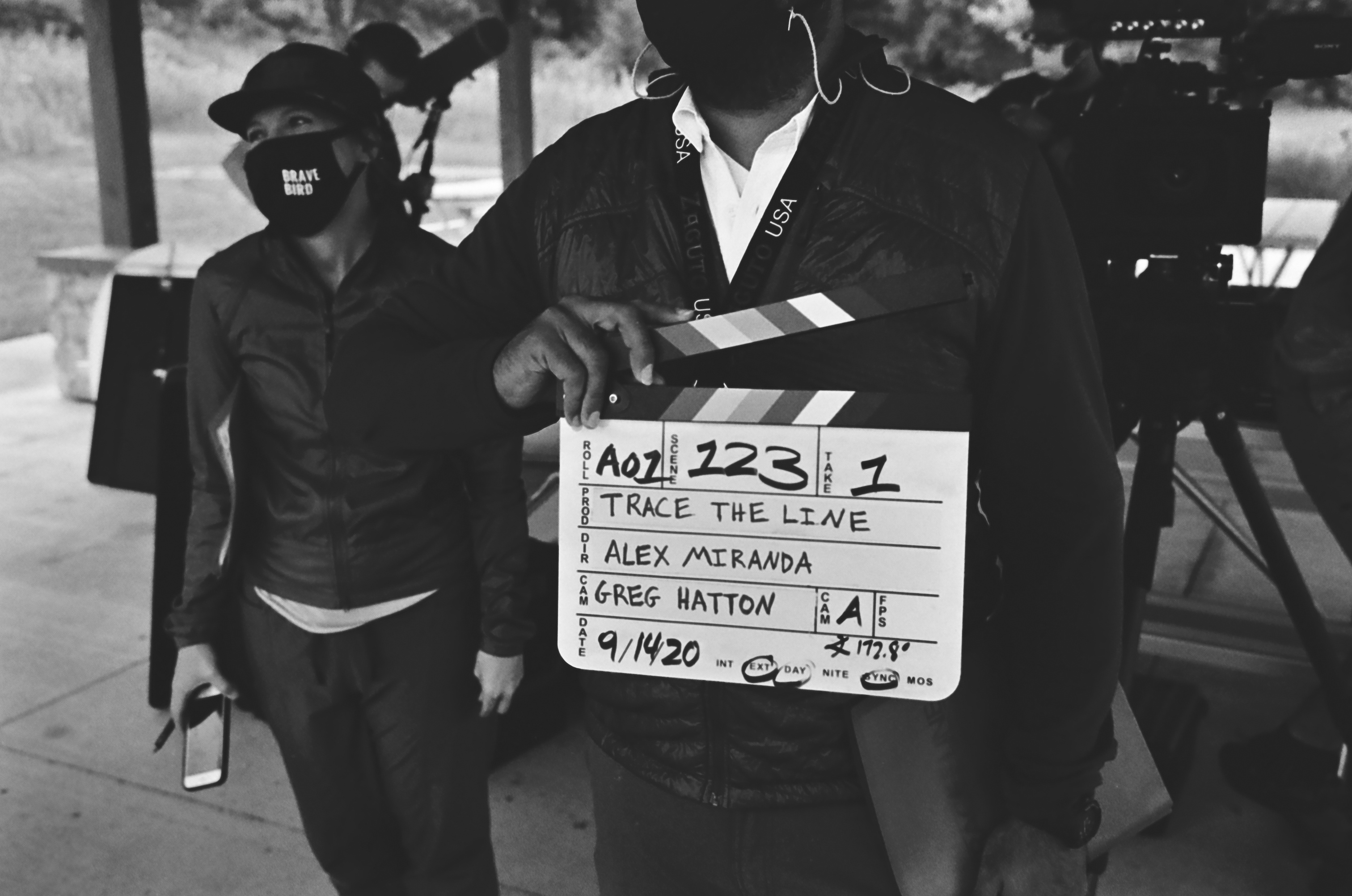 """Behind the scenes with Director Alejandro Miranda Cruz and Producer Noel Miranda holding the slate for """"Trace the Line""""."""