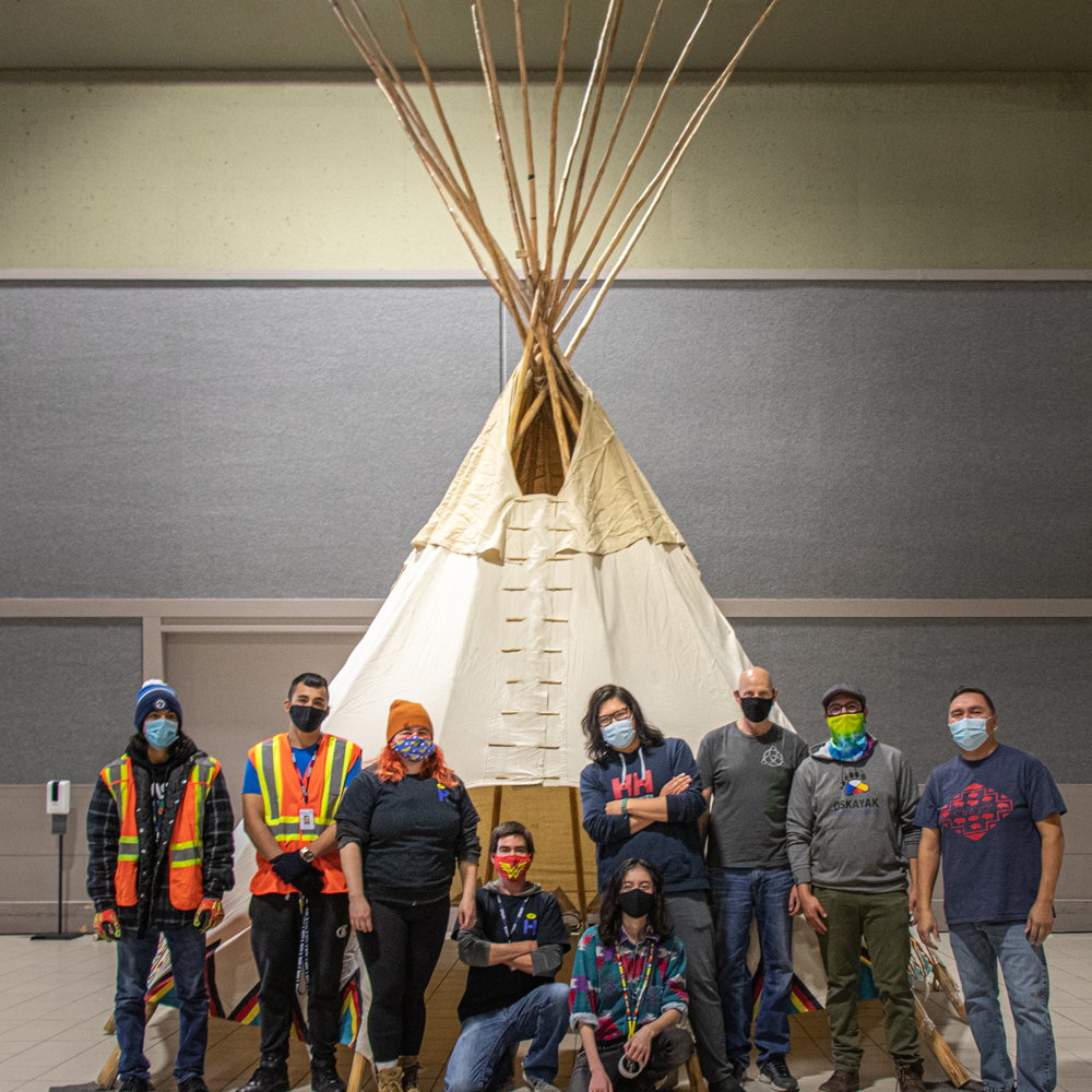 The Hiregood team helps stand Bent Arrow Society's stunning teepee at the Tipinawaw Shelter.