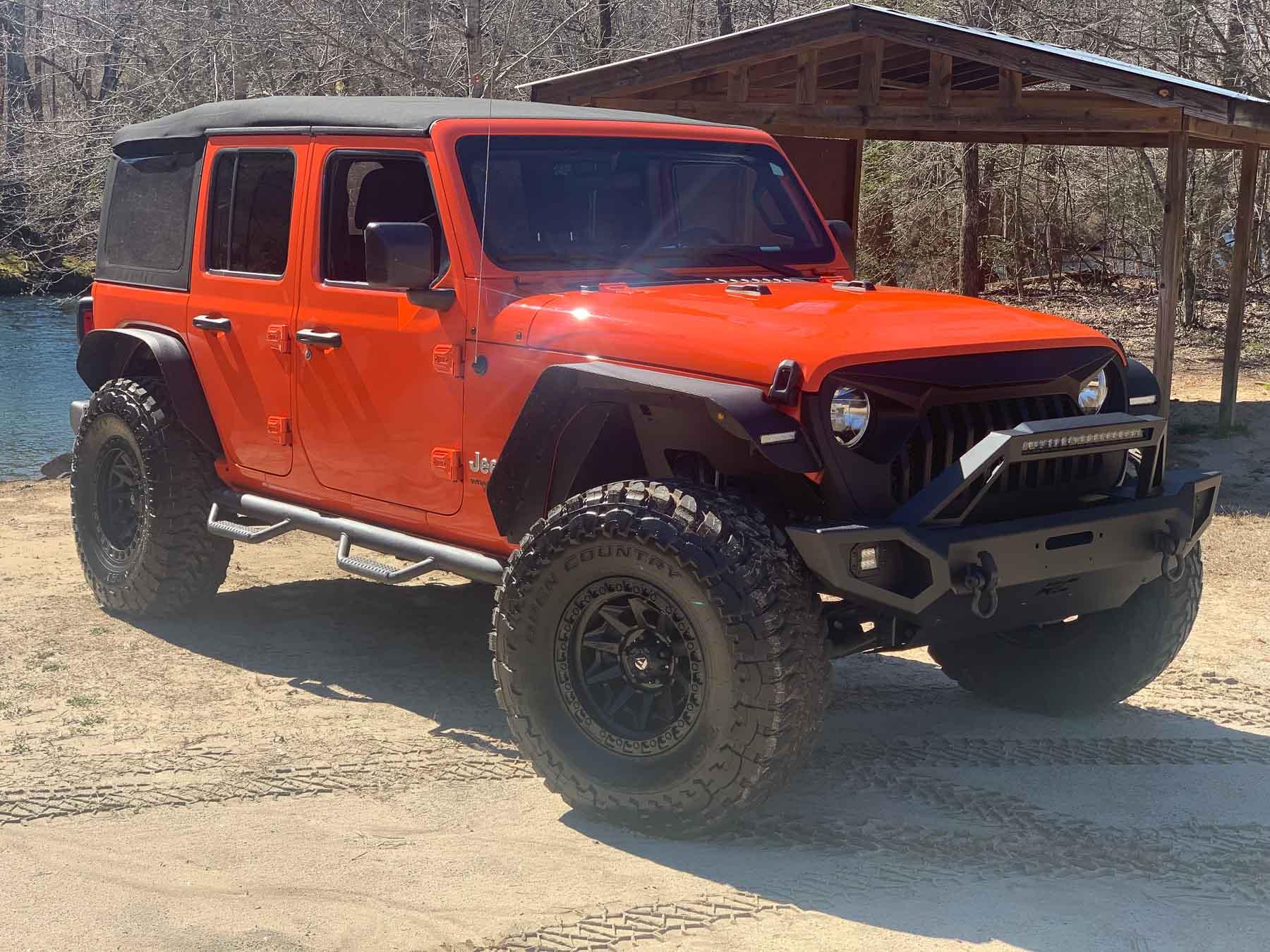 orange jeep by creek side