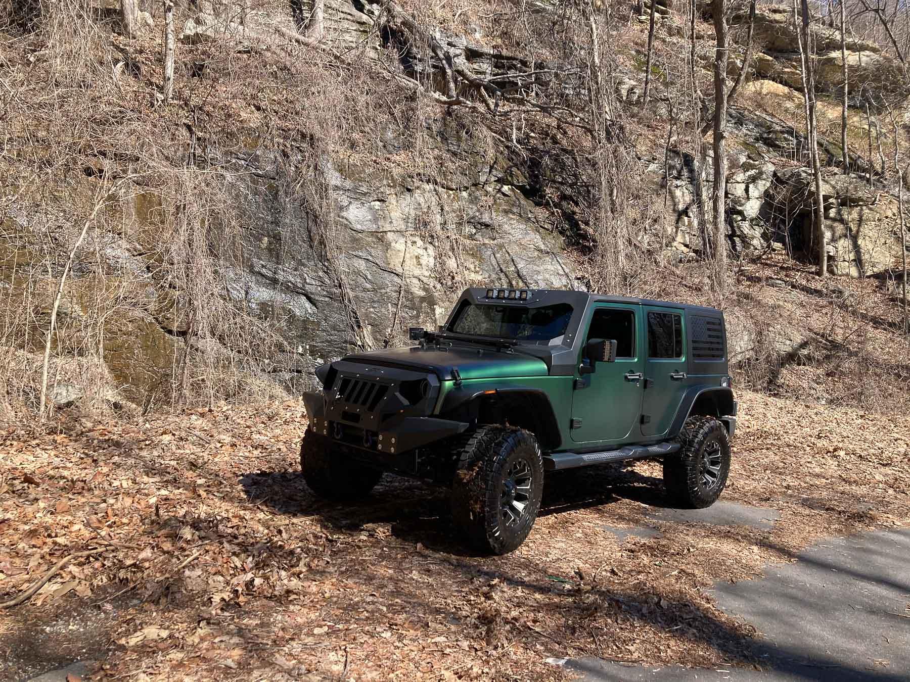 green jeep next to boulder