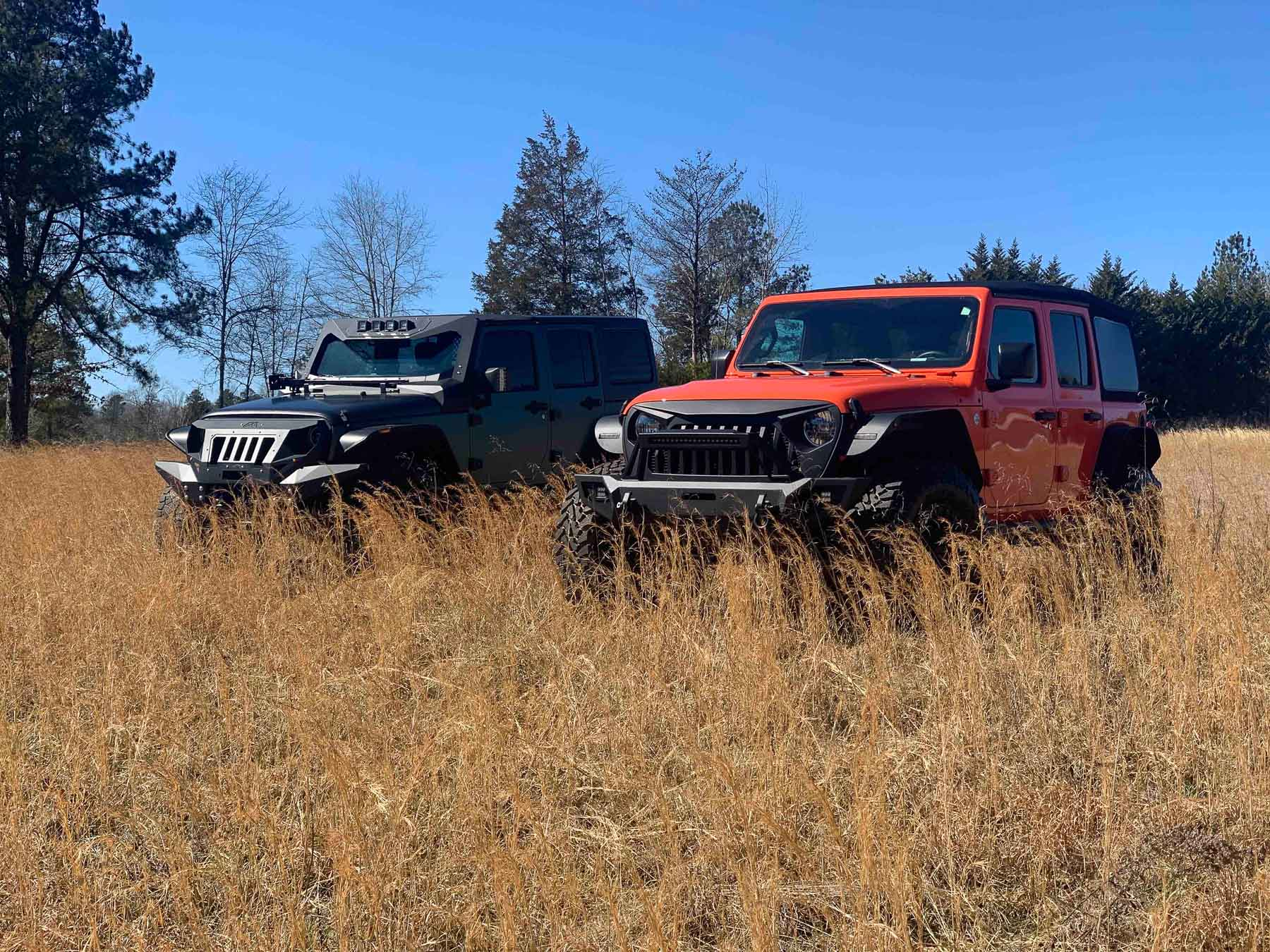 two jeeps in field of grass