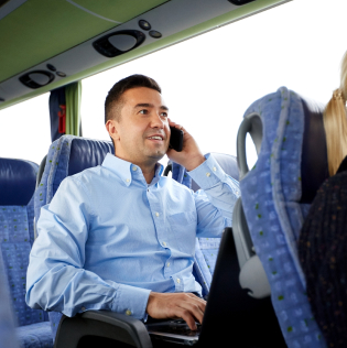 smiling man with smartphone and laptop calling in travel bus