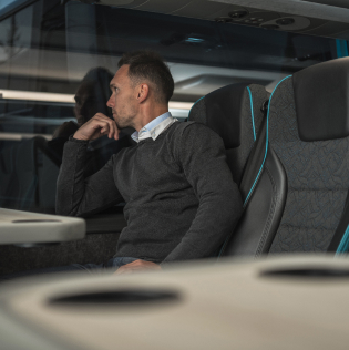 a man sits on a bus seat and looks out the window