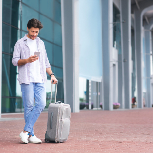 Young Man Standing Near Airport With Smartphone