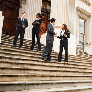 Four well dressed professionals in discussion on the exterior steps of a building.