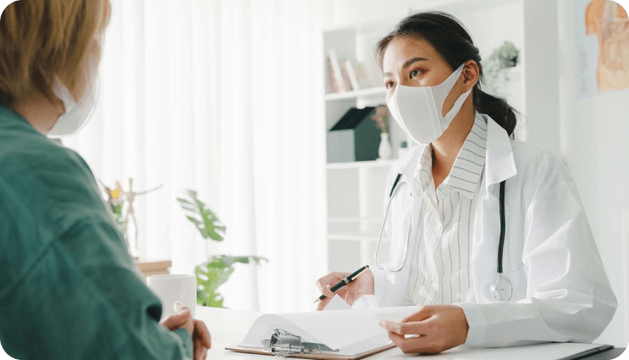 A doctor, wearing a medical mask, is talking to a patient.