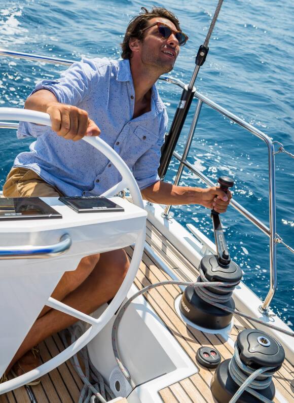Un giovane uomo con gli occhiali da sole manovra in mare aperto uno yacht a vela Oceanis, sorridendo.