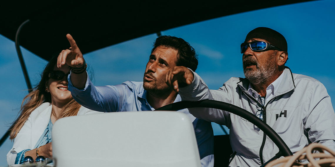 3 membri del team Spartivento discutono su una barca, due degli uomini indicano qualcosa.