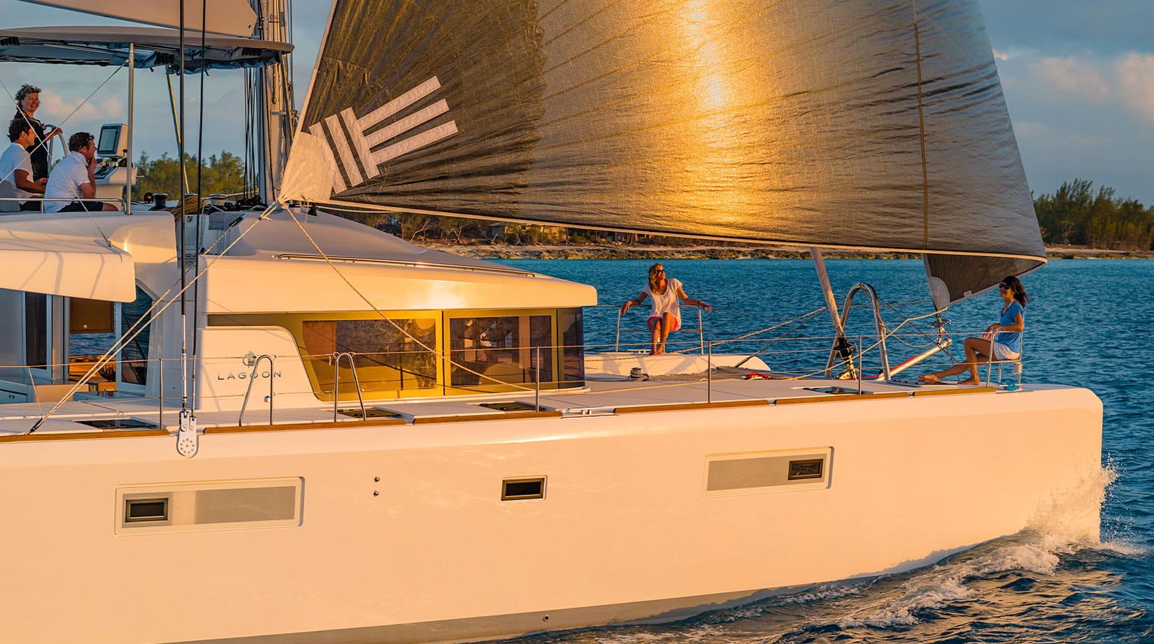Due donne sedute a prua, si godono il tramonto su un catamarano a vela del marchio Lagoon.