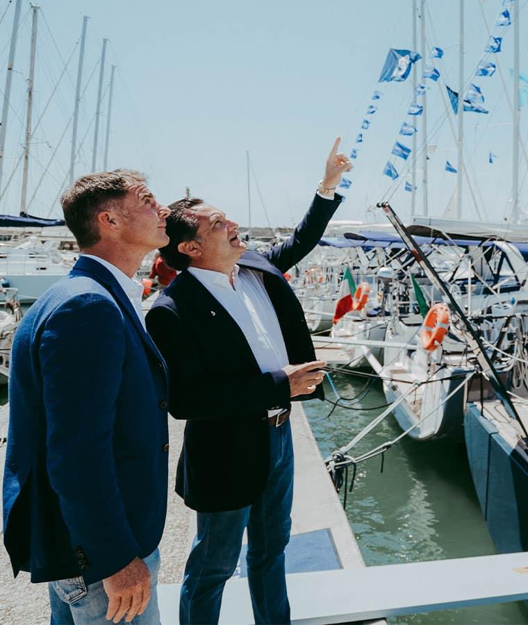 Stefano Pizzi e un altro uomo indicano qualcosa in alto, in una banchina dove stazionano diverse barche a vela Beneteau.