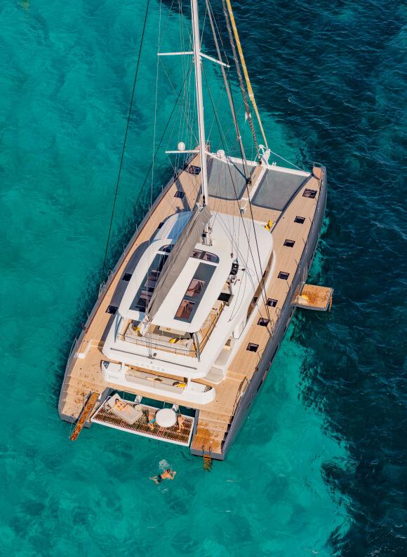 Un catamarano Lagoon stazionato in mare, mentre una famiglia si rilassa tuffandosi in mare e prendendo il sole sulla barca a vela.