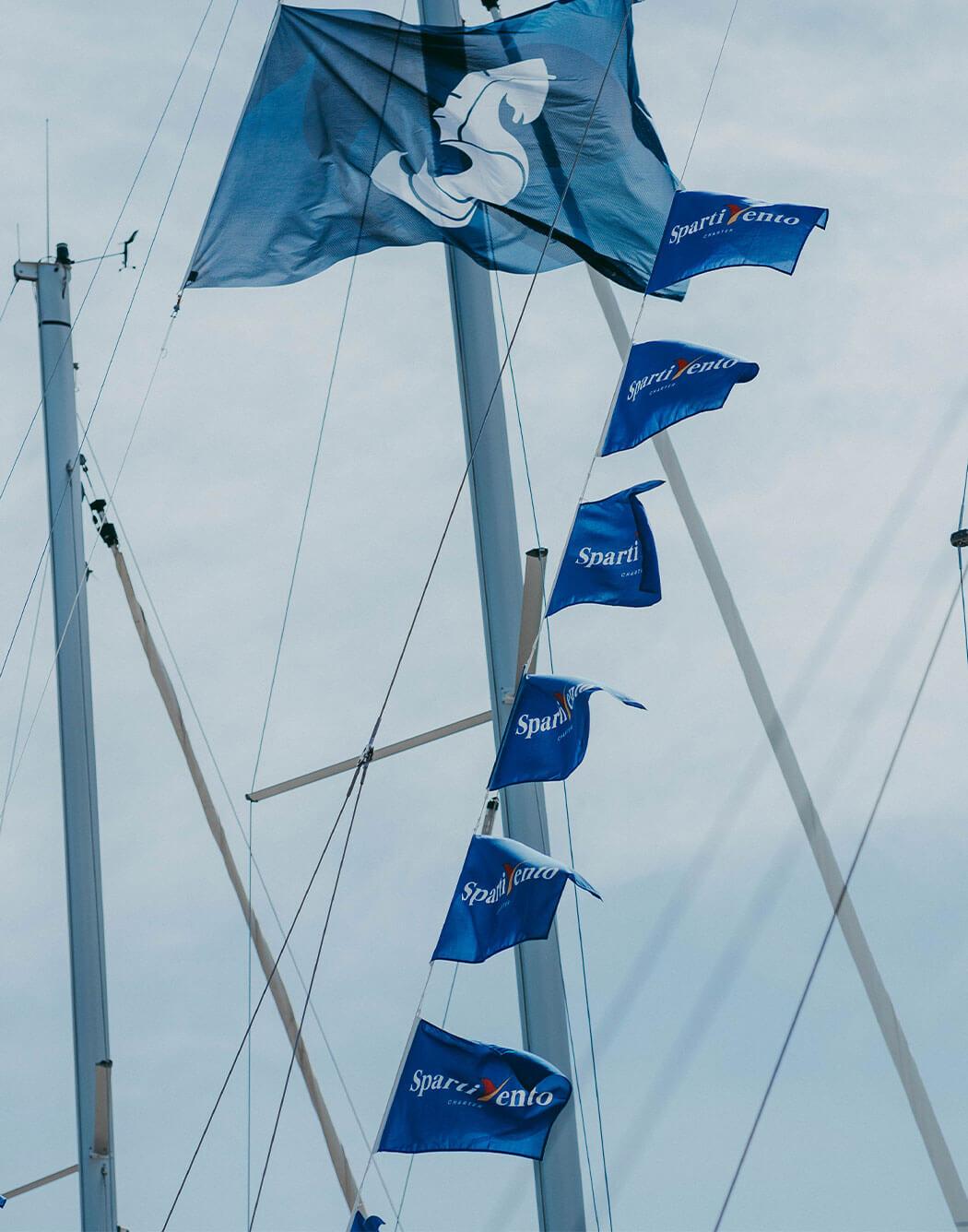 Sei bandiere con il logo di Spartivento Yachts e una bandiera più grande con il logo di Beneteau, sventolano.