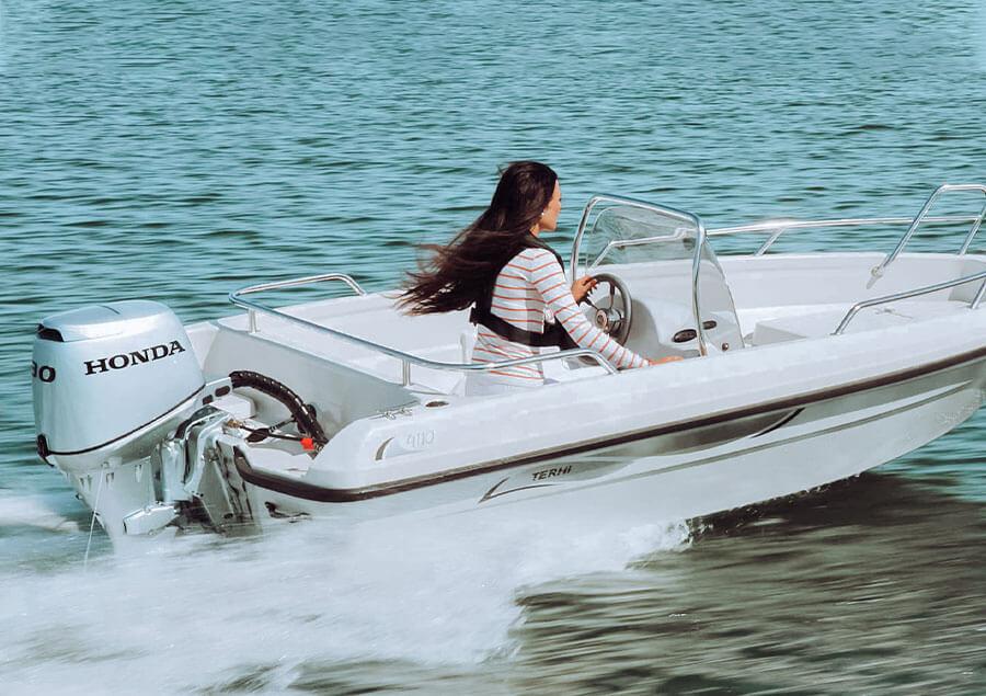 Una donna naviga ad alta velocità sul suo gommone Honda Marine.