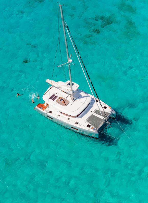 un catamarano a vela stazionato in un mare dall'acqua turchese, mentre un gruppo di persone nuota in mare attorno alla barca a vela.