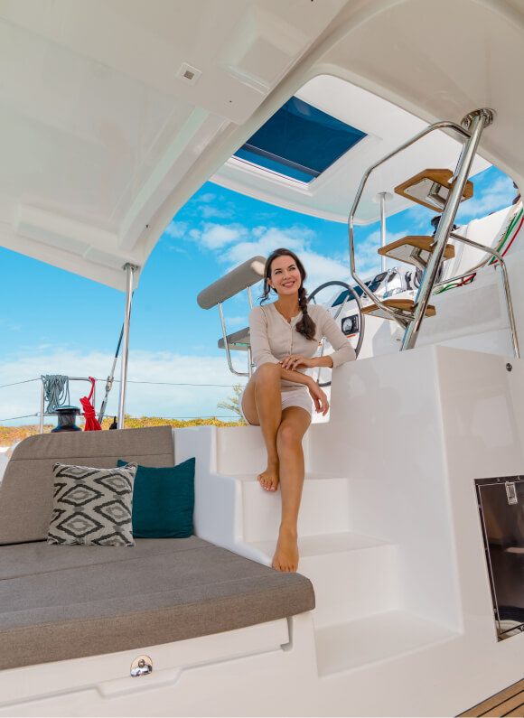 Una donna seduta sorride nella zona living a poppa di una barca a vela di Beneteau.