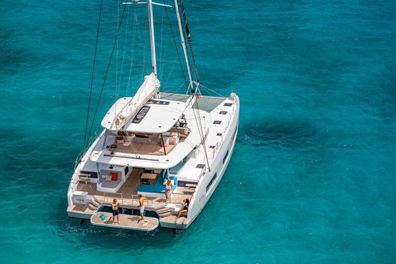 Un catamarano staziona in un mare verde acqua, mentre un gruppo di persone si gode la vita a bordo.