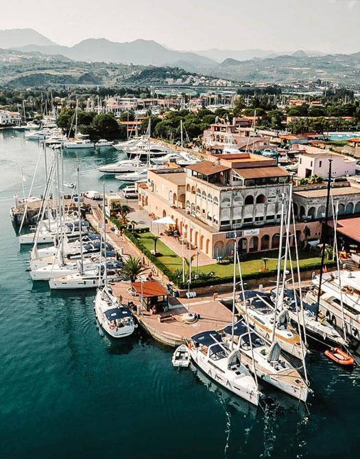 Vista aerea della sede di Spartivento Yachts a Marina di Portorosa, con delle barche a vela stazionate nel porto.