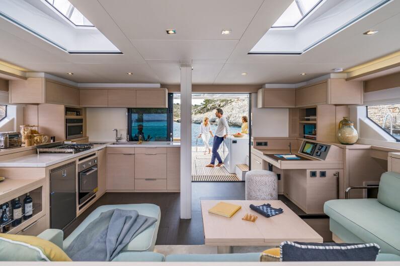 L'interno di uno yacht del gruppo Beneteau, in cui si vede il salotto fornito di cucina e divani.