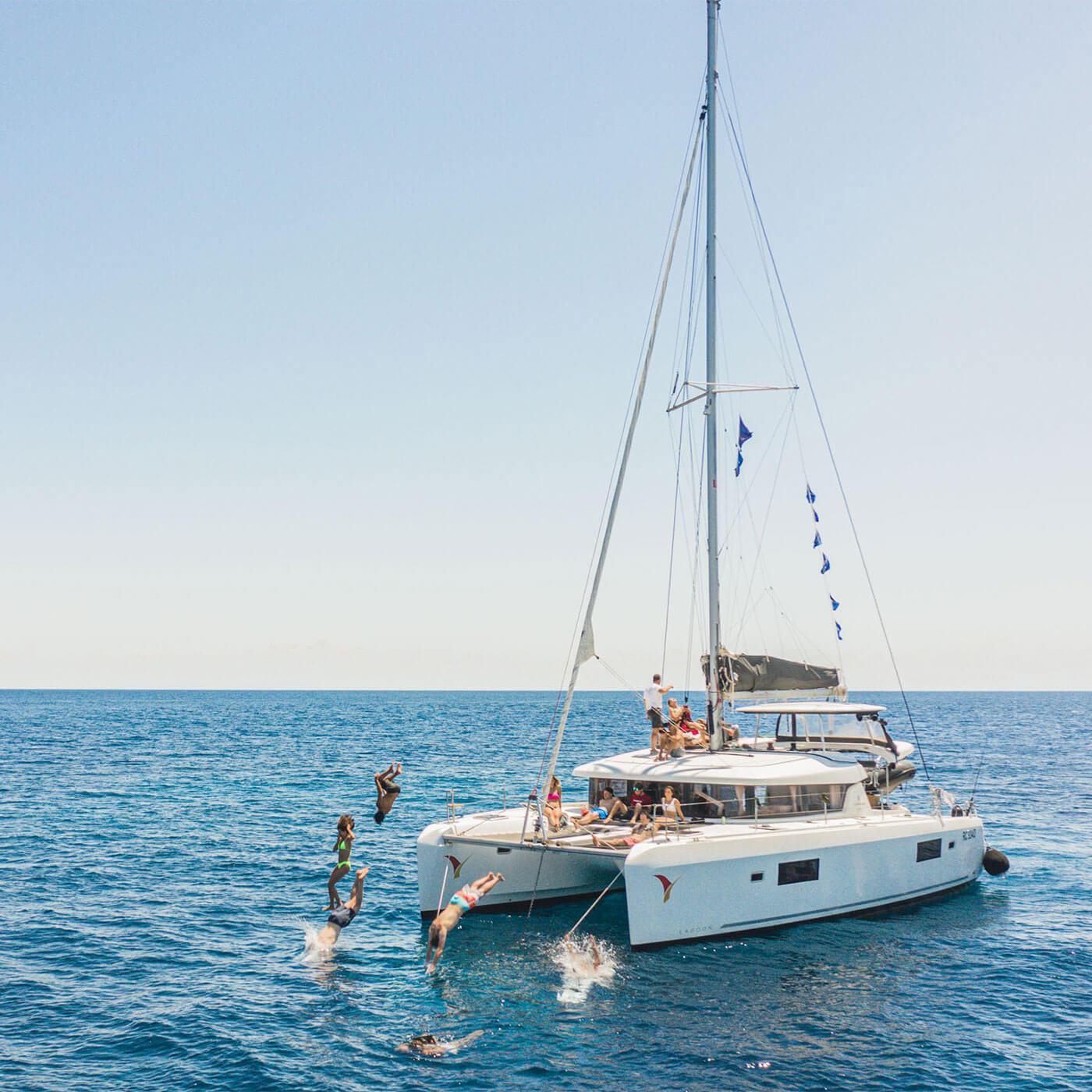 Un gruppo di persone si tuffa in mare saltando da un catamarano a vela.