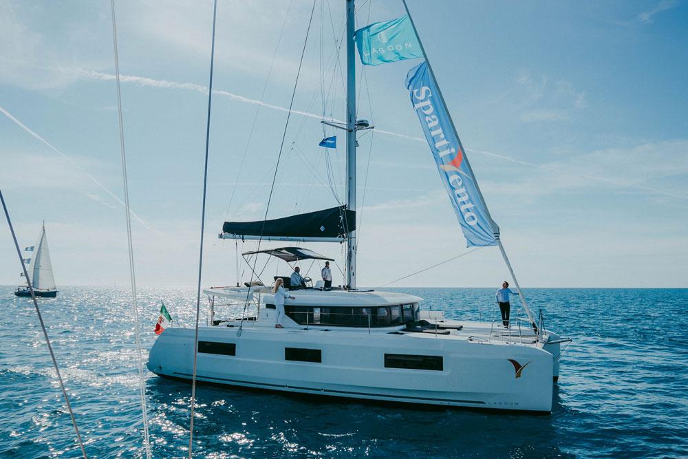 Un catamarano Lagoon in mare, con una vela blu su cui c'è il logo dell'azienda Spartivento.