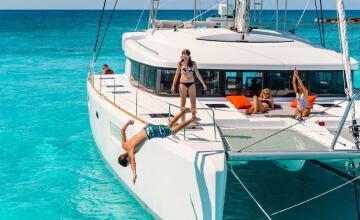 Due ragazzi si divertono tuffandosi in un mare turchese dal catamarano a vela Lagoon.
