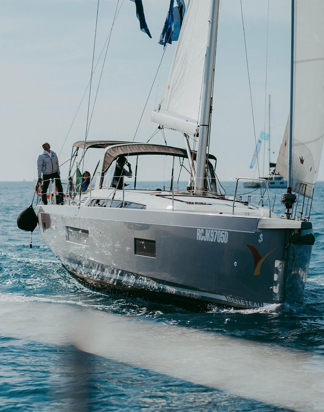 Vista frontale di una barca a vela Beneteau che naviga in mare con 3 persone a bordo.