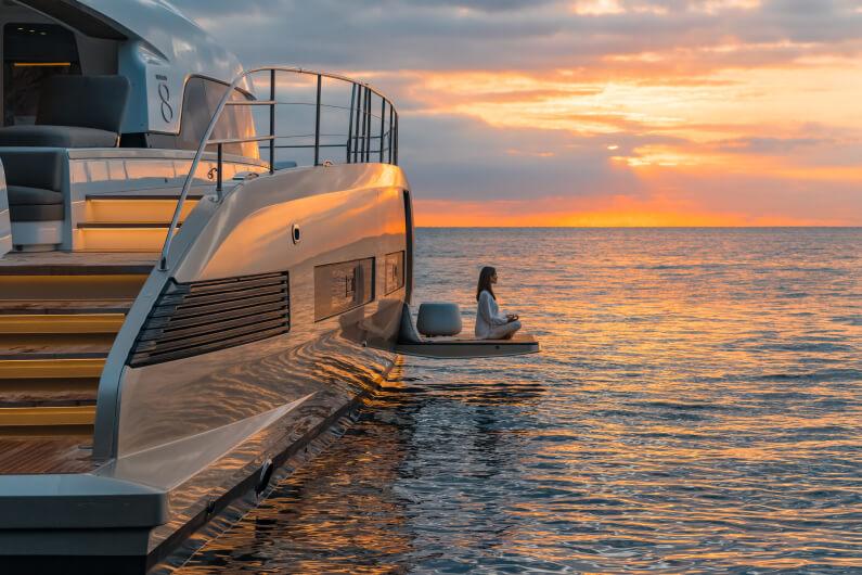 Una donna fa meditazione sulla piattaforma esterna del catamarano a motore Lagoon durante il tramonto che colora l'acqua e il cielo di arancione e viola.
