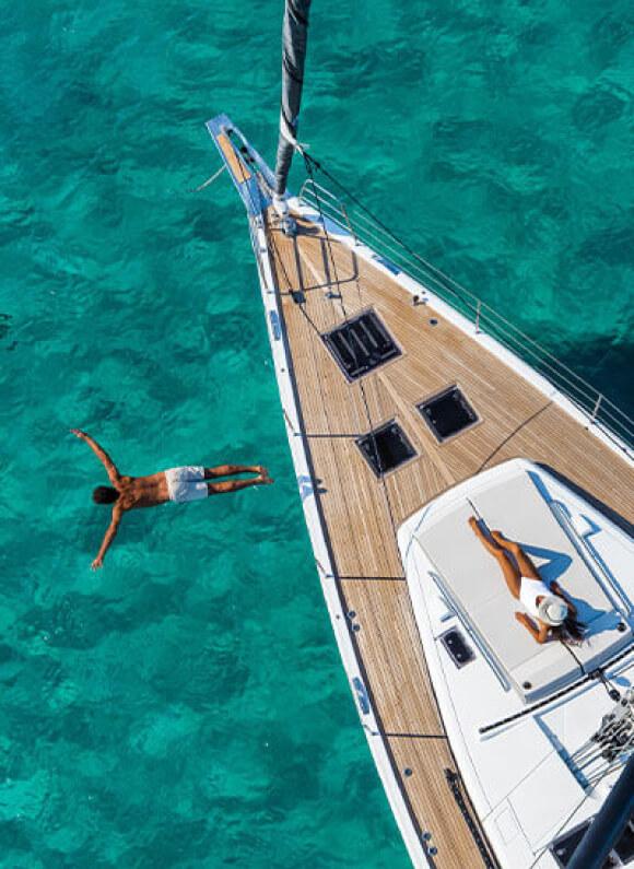 Un uomo si tuffa in un mare verde acqua, dallo yacht a vela Oceanis di Beneteau, mentre una donna prende il sole a prua.