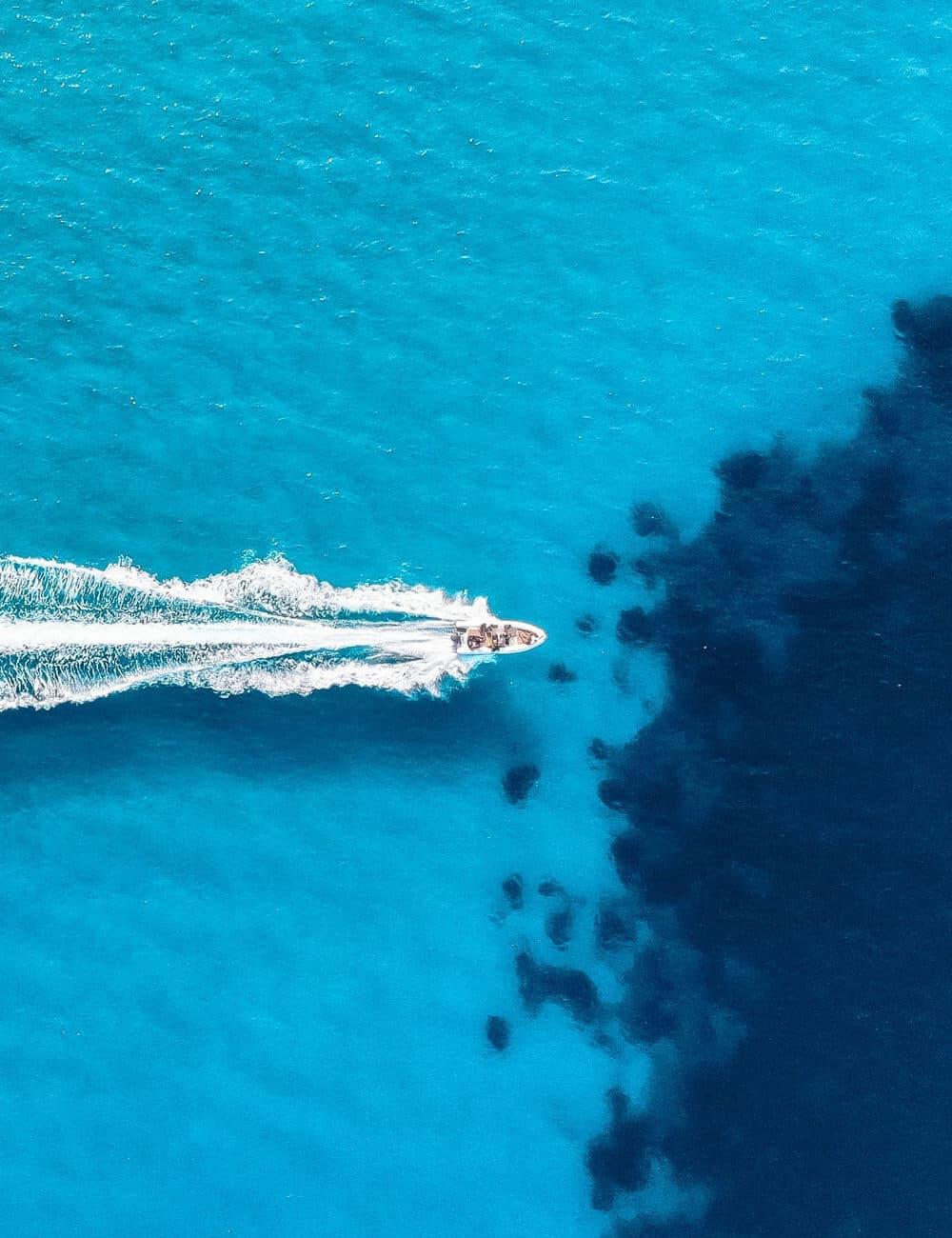 Una vista aerea di un gommone che naviga in mare aperto e lascia una scia di schiuma alle sue spalle.