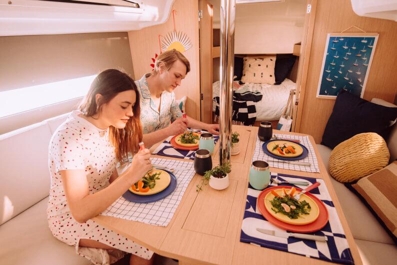 Una giovane coppia consuma un pasto seduta a tavola, a bordo di uno yacht.