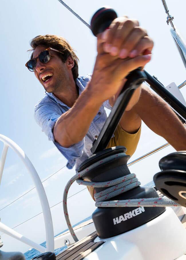 Primo piano di un uomo con gli occhiali da sole sorride cazzando la vela sulla sua barca a vela.